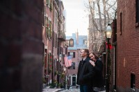 A couple poses for a photograph at the top of Acorn Street in Boston Massachusetts during there engagement session