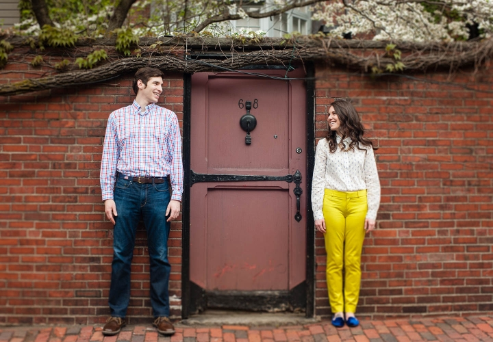 A colorful young couple poses against a deep red brick wall  standing at either side of an iron framed red door during there engagement session