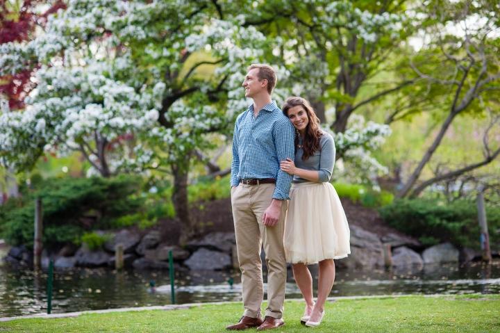 A cute couple poses in front of gorgeous spring flowers during their engagement session