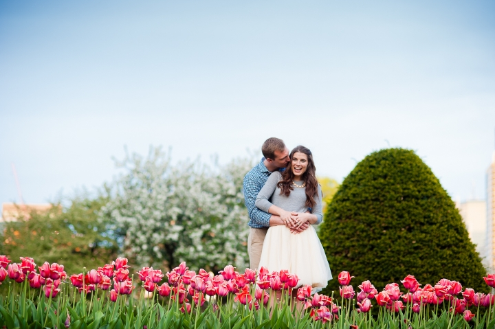Cute Couple poses in front of beautiful red tulips during their engagement session in Boston Gardens