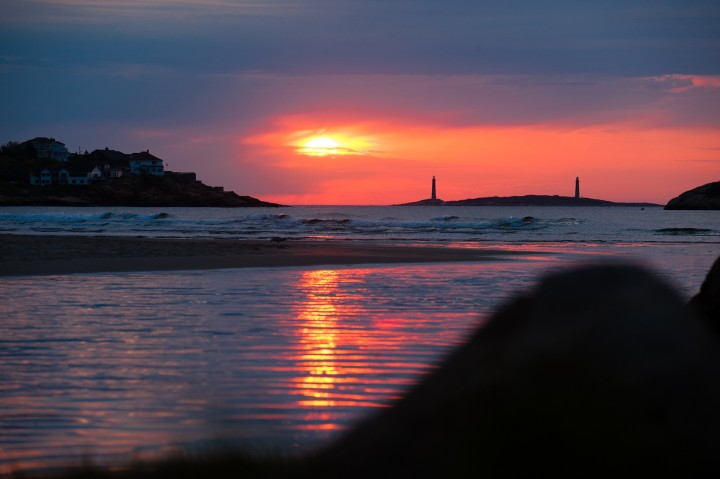Twin lighthouses are silhuetted at sunrise of Good Harbor beach in Gloucester ma