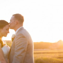 An amazing golden sunset over a marsh behind a couple during there wedding day couples portraits