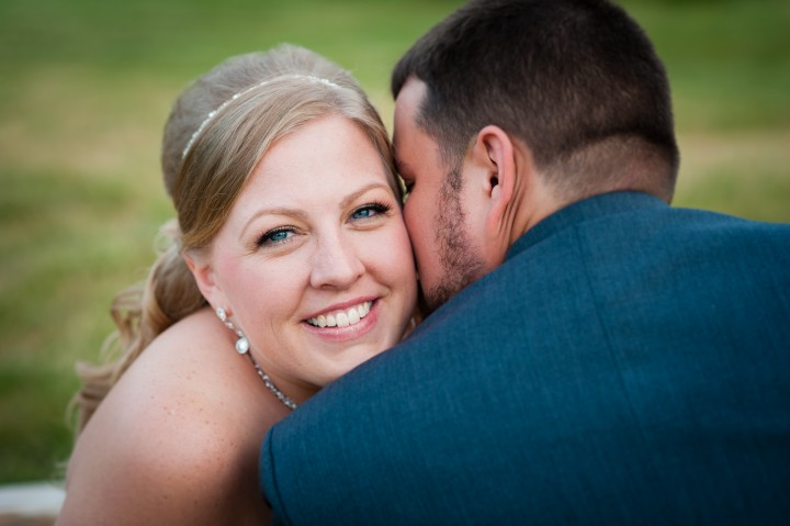 Groom kisses his smiling bride on the cheek after there wedding ceremony