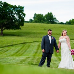Bride and Groom holding hands in a large green field