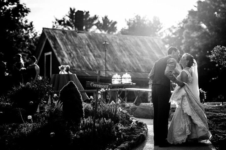 Black and white of Bride and groom kissing at their barn wedding reception