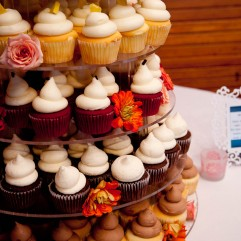 Four tiers of colorful cupcakes on a white table waiting for wedding guests to dig in