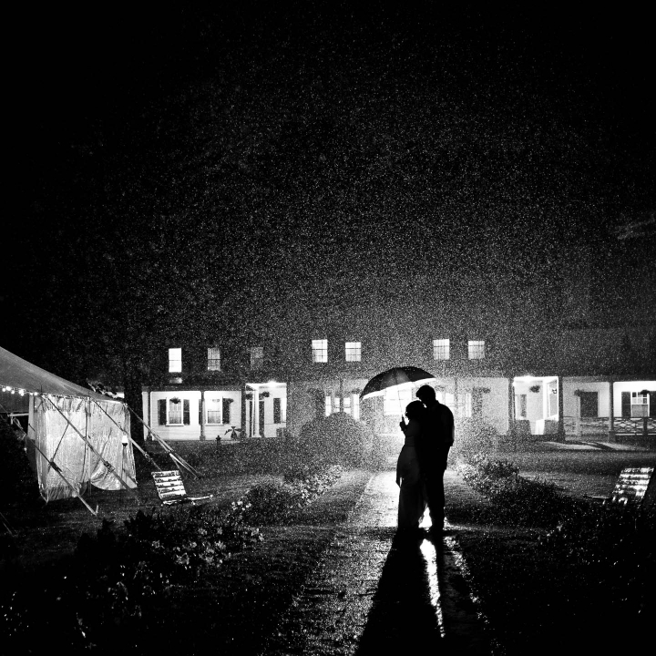 Black and white image of a bride and groom standing under an umbrella in the rain on their wedding day at night in front of their venue