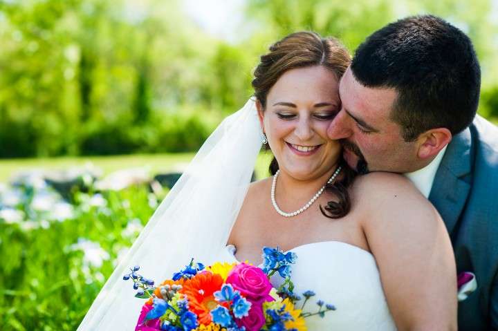 Bride and groom embrace in the shade on their sunny vineyard wedding day