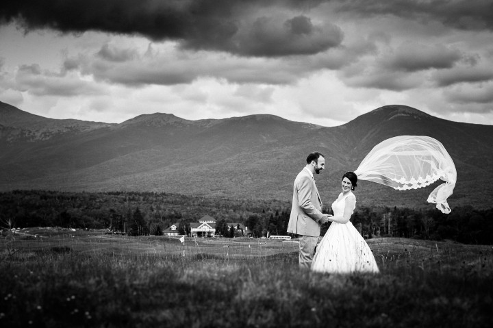 Gorgeous bride and her groom stand in a field with the brides veil blowing in the wind