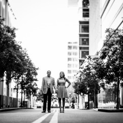 Black and white image of adorable couple standing in treelined street