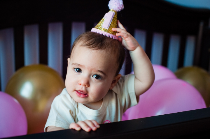 Cute 1 year old girl trying to pull her crown off her head