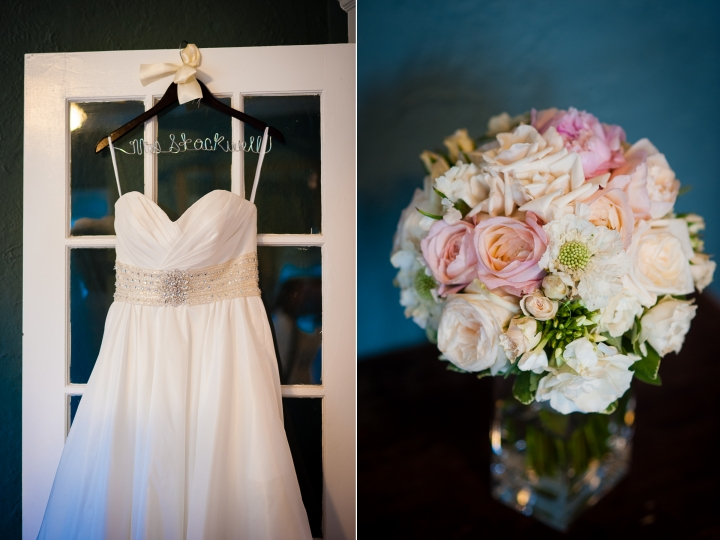 beautiful wedding gown hangs against white door while a stunning bouquet is shown on a wooden table