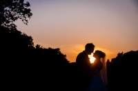 Bride and Groom silhouetted in front of gorgeous sunset during their destination wedding