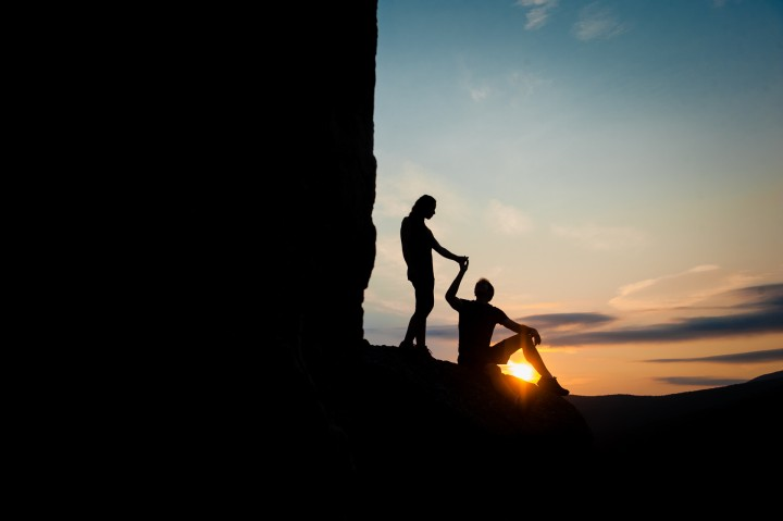 Mountaintop sunrise silhouette of recently engaged couple