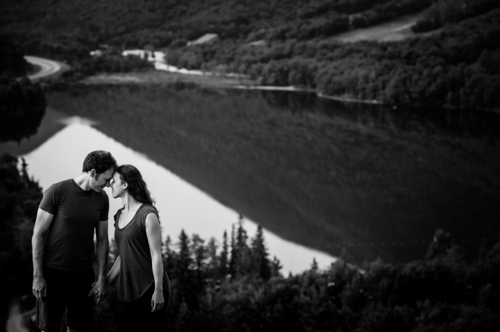 adventurous couple stands on mountain top with a mountain lake behind