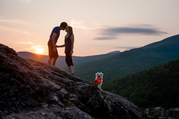 adventurous dog with his newly engaged owners pose on the edge of cliff  at sunrise