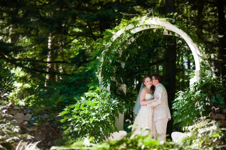 gorgeous couple pose under beautiful garden trellis in the woods during their estate wedding