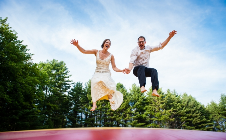 fun adventurous bride and groom jumping on a big air bounce in wedding attire