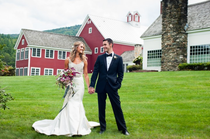 bride and groom holding hands in front of gorgeous red barn