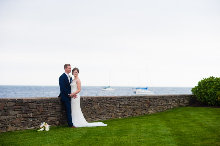 bride and groom stand on the wychmere beach club lawn with the gorgeous ocean behind