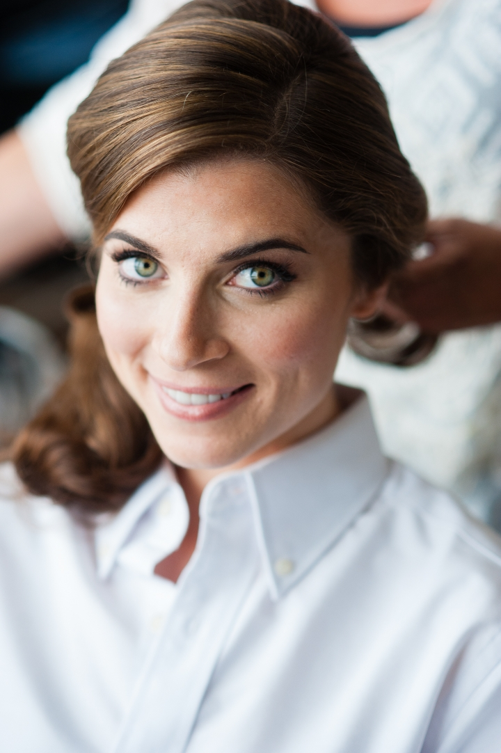 gorgeous bride with green eyes smiles at camera while her hair is getting styled
