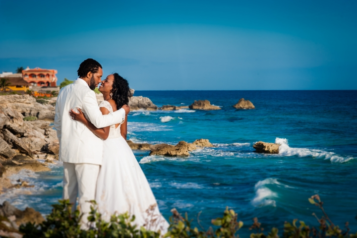 isla mujeres wedding bride and groom kiss on rocky coastline