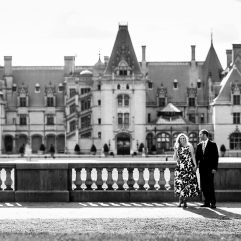 engaged couple poses for engagement photo in front of Biltmore Mansion