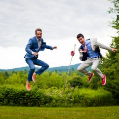 two guys jump for joy at their backyard asheville wedding