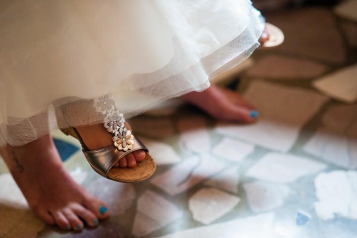 Flower girls little feet dangling as she sits on brides lap