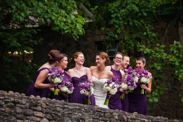 the bride and her ladies in purple bridesmaid dresses on the bridge at Montreat College