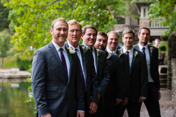 handsome groom and groomsmen pose for a moment on the bridge at Montreat College