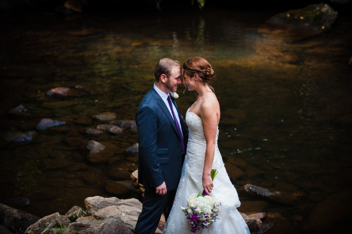 bride and groom take a quiet moment by the river