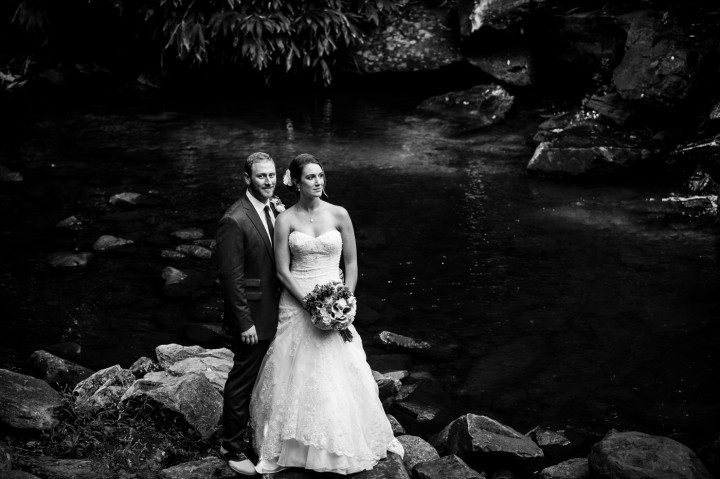 Adventurous couple poses on their wedding day on the rocks by the stream at Montreat College