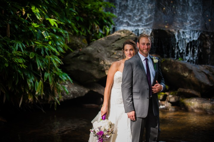 adventurous bride and groom on the rocks in front of a waterfall in the mountains of NC