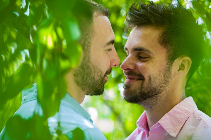 Surrounded by the green foliage of the tree that they are standing under this gay couple seems to enjoy a moment alone duing there Arnold Arboretum engagement session