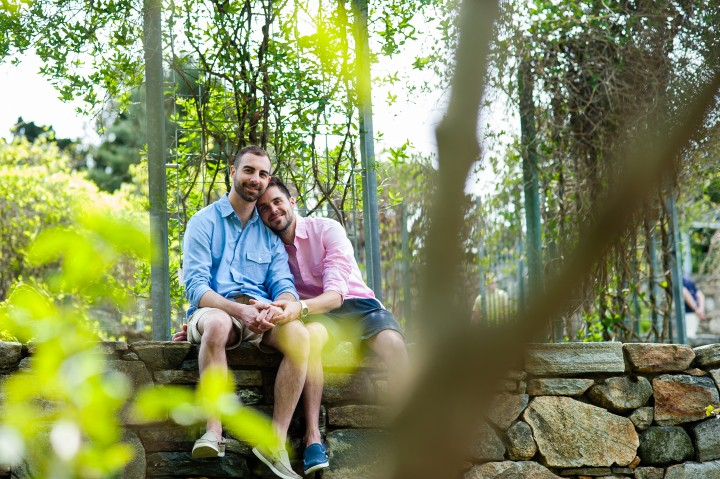 A gay couple sits on top of a stone wall holding hands during there Arnold Arboretum engagement session