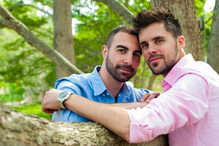 Lokking at the camera and embracing while posing for an image during there Arnold Arboretum engagement session