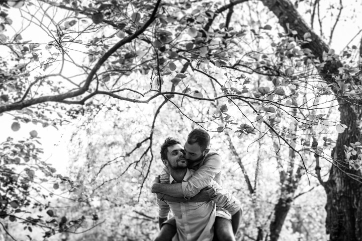 A black and white image of a couple enjoying a piggy back ride during an engagement session in the Arnold Arboretum near Boston Massachusetts