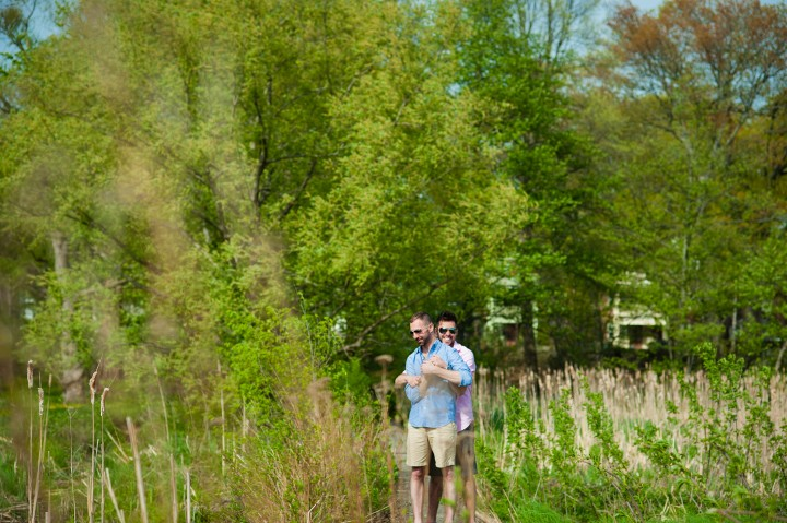 In a filed of green this couple poses with sunglasses on duing there Arnold Arboretum engagement session