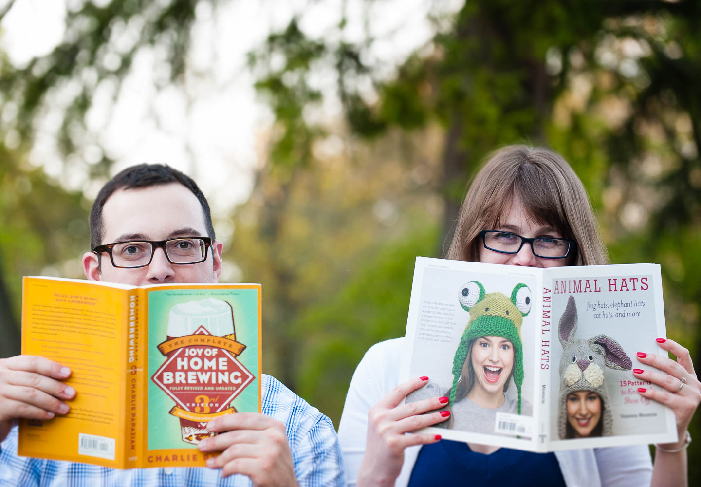 A quirky young couple peering over the top of there self chosen books for an engagement session image