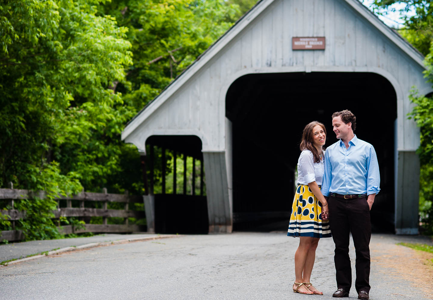 a couple poses in front of a covered bridge in Woodstock Vermont