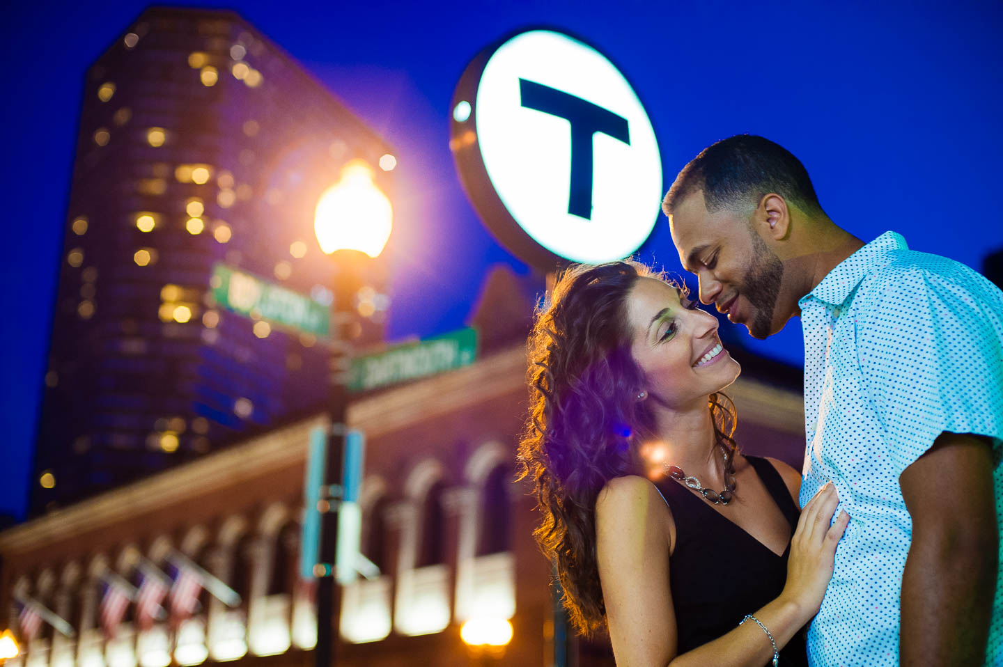 A visibly passionate couple poses near the Copley T stop in Boston Massachusetts with the Boston Public Library in the background at night