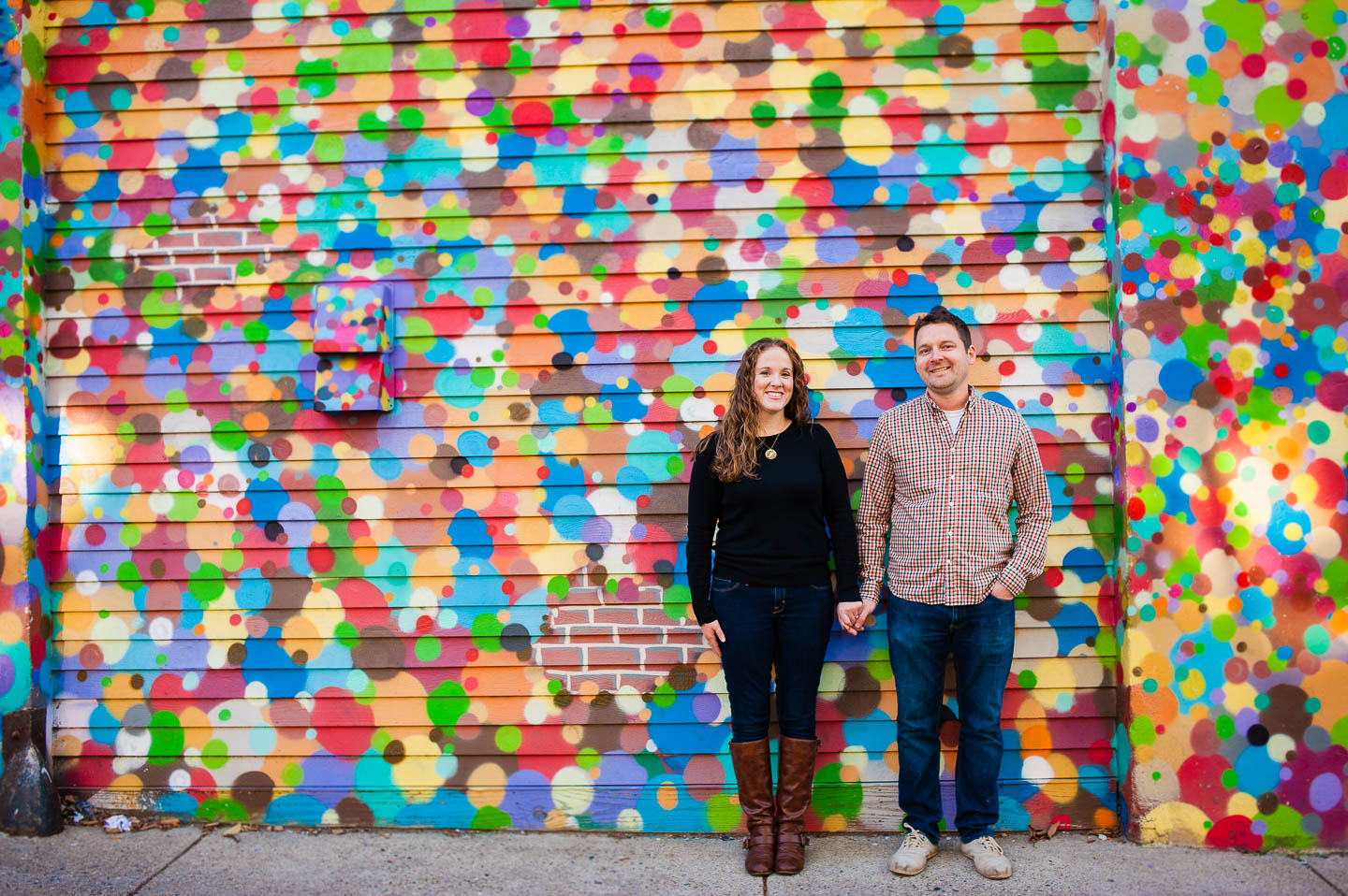 A beautiful couple poses in front of a vibrant colorful polka dot painted brick wall during there engagement session in Cambridge Massachusetts