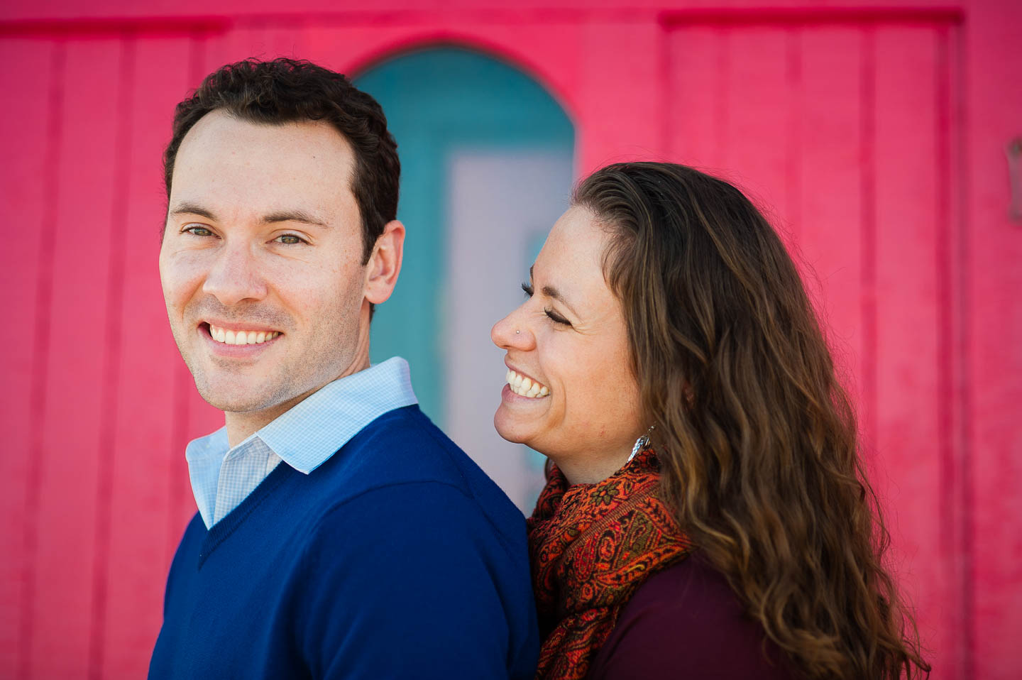 Attractive couple posing in front of a vibrant red barn board wall on Cape Cod during there engagement session