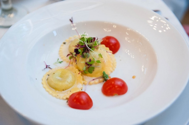 Wedding appetizer with Ravioli and cherry tomatoes on a white plate
