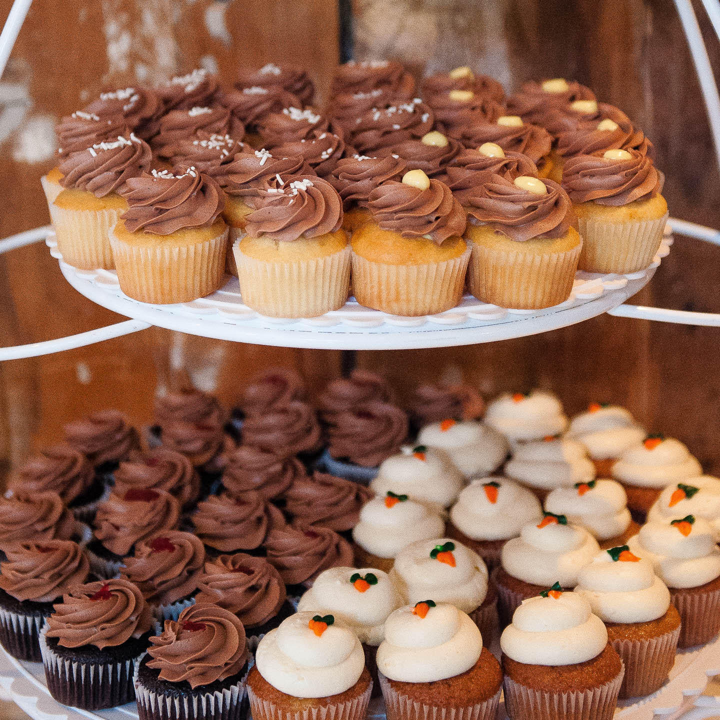 An assortment of cupcakses on a rack at a wedding