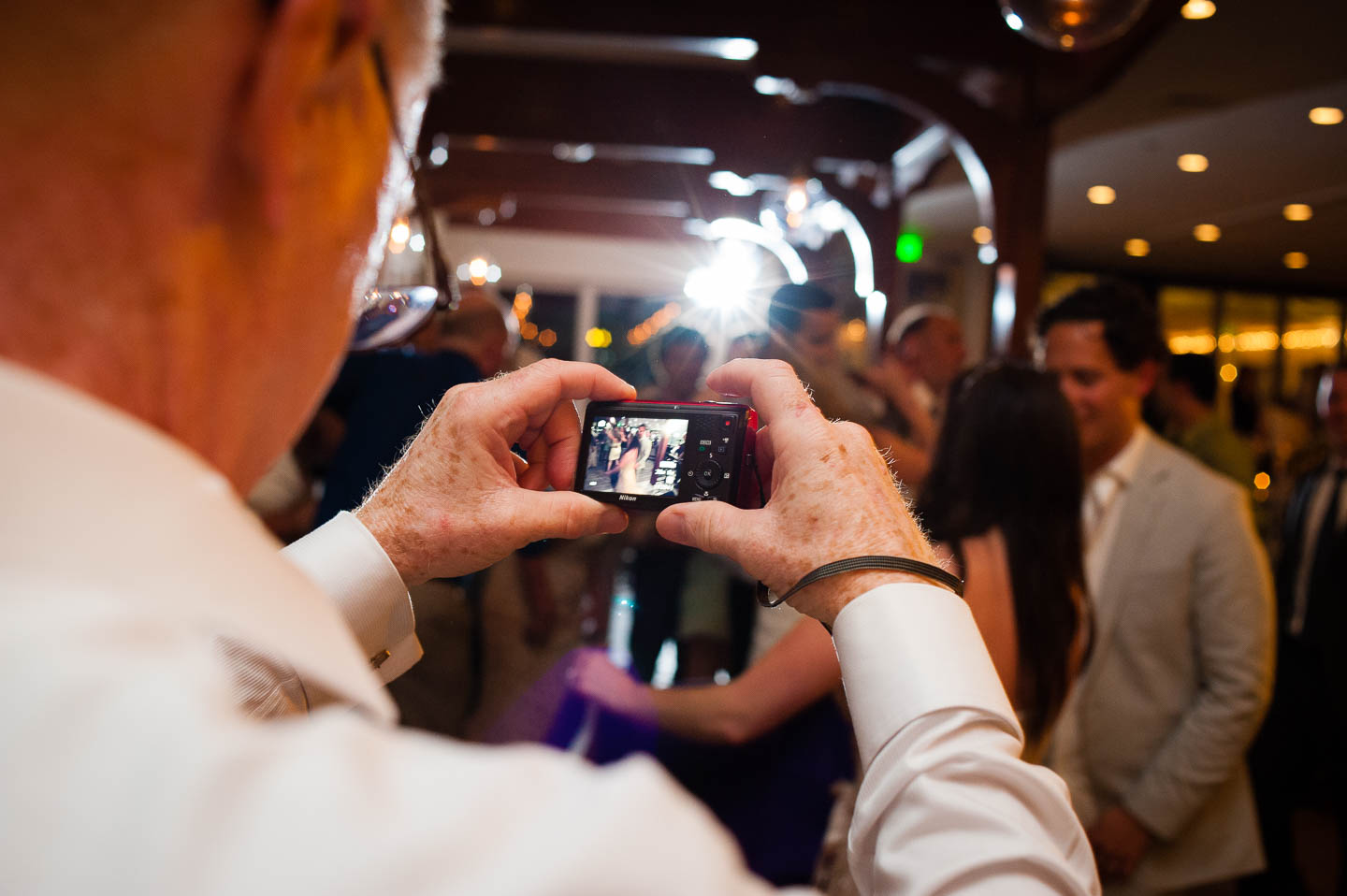 Wedding photograph taken over the shoulder of a guest with a point and shoot camera