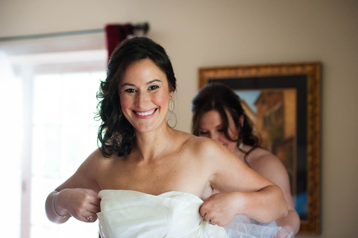 A beautiful bride smiling at her Asheville wedding photographer on her wedding day while getting into her dress