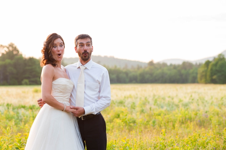 Bride and Groom posing for photo on their wedding day with shock and aww on their face as something surprising happens off camera