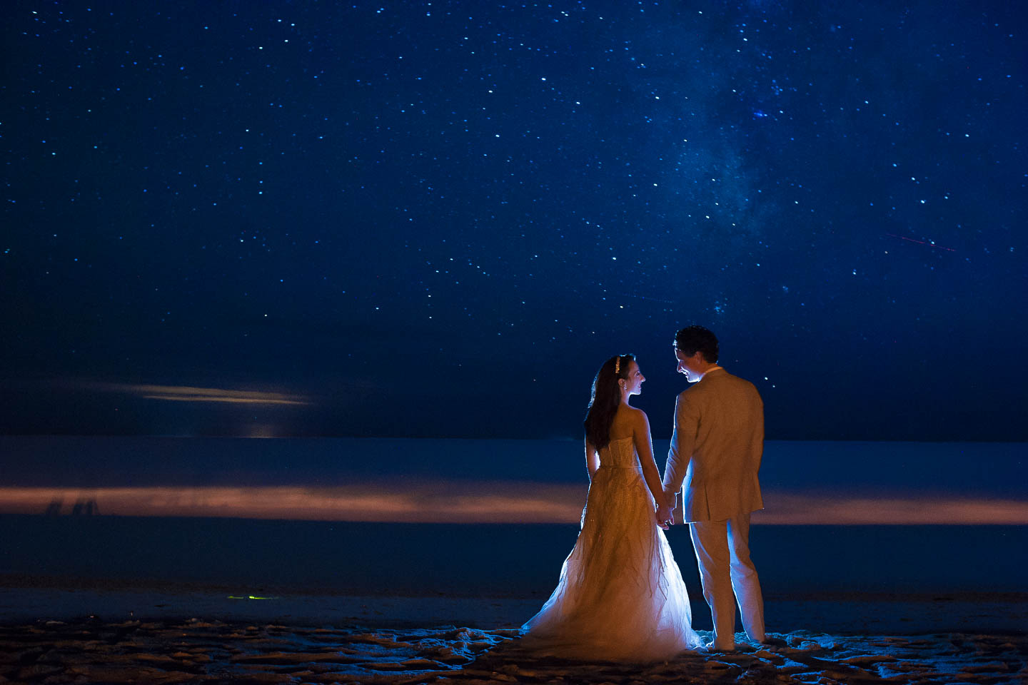 A night image of a couple on the beach after their wedding